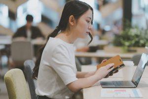 カフェでスマートフォン学習をする女性
